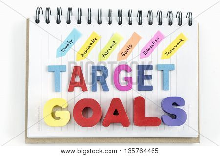 Alphabet letters wood words goals target and handwriting timely achievable  relevant goals education teamwork on notebook over white background, business success concept