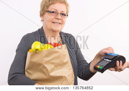 Senior Woman Holding Shopping Bag And Using Payment Terminal With Contactless Credit Card, Paying Fo