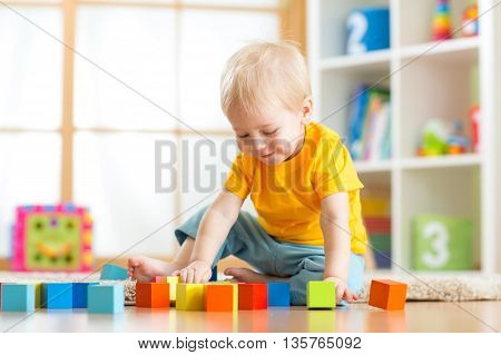Preschooler child playing with colorful toy blocks. Kid playing with educational wooden toys at kindergarten or day care center. Toddler in nursery room.