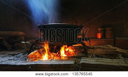 Native image pot of food on burning fire.