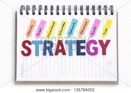 alphabet letter wood words strategy on the notebook with handwriting stability target retrenchment achievable teamwork education growth yield over white background, Business strategy concept
