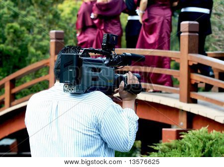 A photo of a videographer filming a wedding