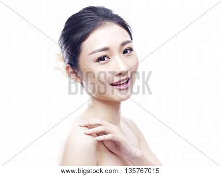 studio portrait of a young asian woman looking at camera smiling side view isolated on white.