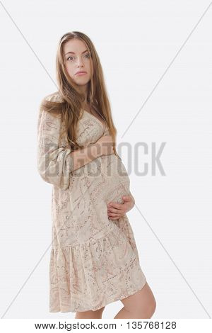 Puzzled, upset pregnant woman holding her belly in a bright dress with long blond hair on white background