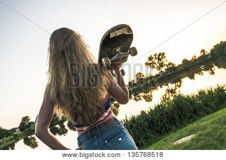 Awesome skateboarder girl with skateboard posing outdoor. Skateboarding at Summer.