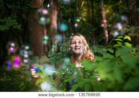 Young girl in the forest playing with soap bubbles