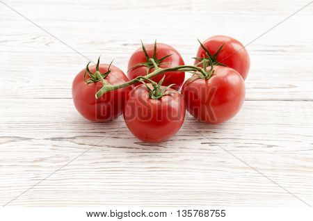 Tomatoes. Branch of red tomatoes on white wooden background. Close up perspectives