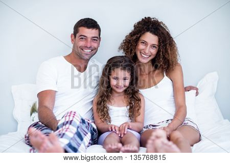 Portrait of a family sitting together on bed at home