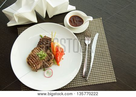 Cooked pork chop on a white plate