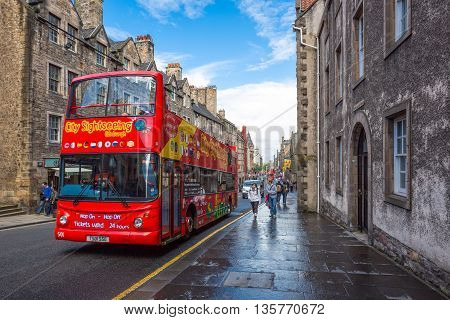 Edinburgh Scotland - July 28 2012: People near a tour bus in the Royal Mile looking towards Holyrood.