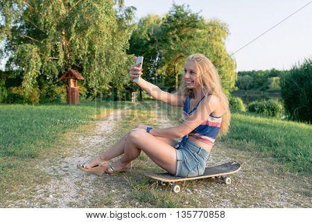 Young skateboarder girl taking self portrait