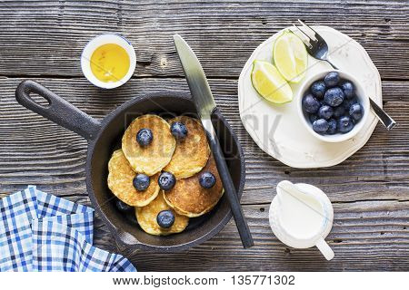 Healthy summer breakfast. Cast iron black frying pan with fresh hot peshnichnymi oat pancakes with blueberries and liquid honey on a dark wooden background.