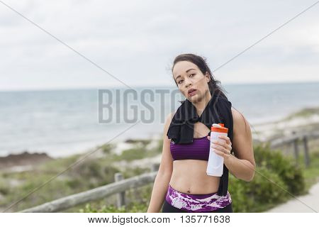 Attractive young brunette cooling down and drinking water from a bottle after working out on the beach