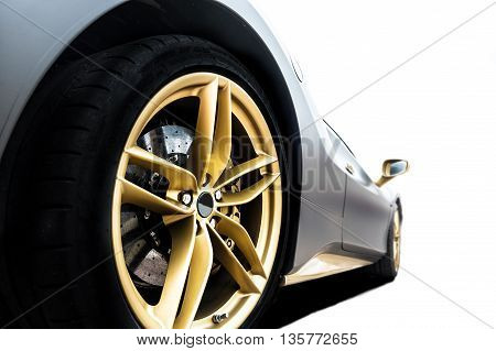 Close up of a tire of a black car with golden rim