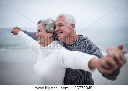 Happy senior couple standing with arms outstretched on the beach