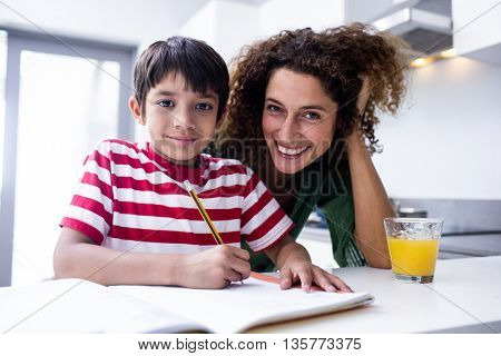 Happy mother helping son with homework in kitchen