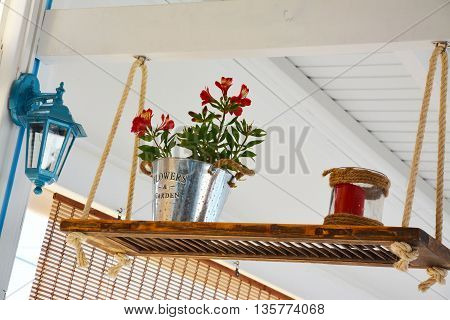 Red flowerpot put on a support held by a rope