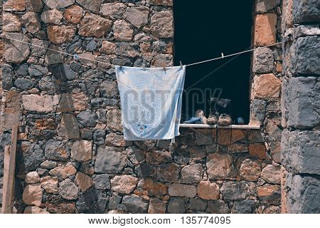 A towel hanging to dry near a window with some worn boots