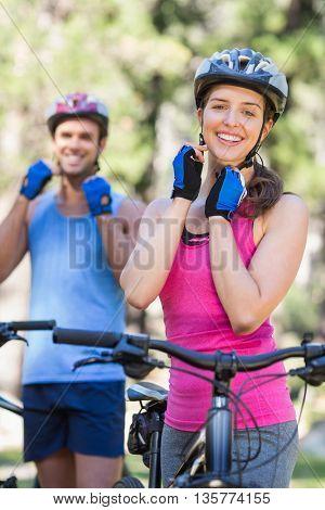 Portrait of happy female and male bikers wearing helmet