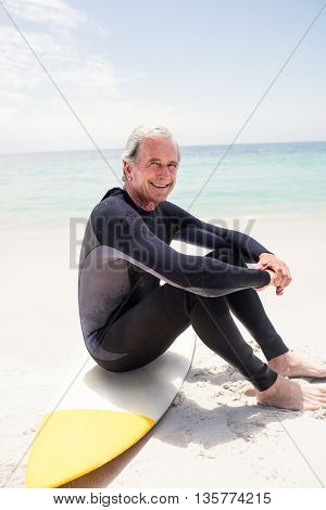 Portrait of happy senior man in wetsuit sitting on surfboard at beach
