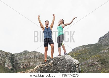 Excited young couple standing on rock against sky