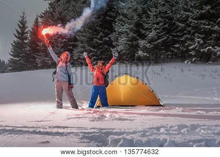 Two backpackers asking a help with rescue signal fire in a winter field