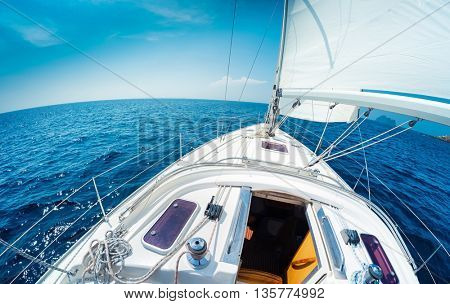 Sailing vessel moving with sail in the open sea