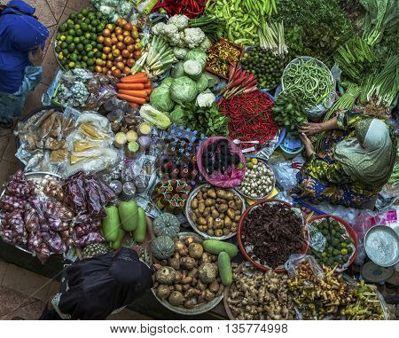 Old muslim woman selling fresh vegetables in traditional asian market