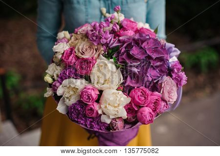 girl holding a bouquet of purple and white flowers no face
