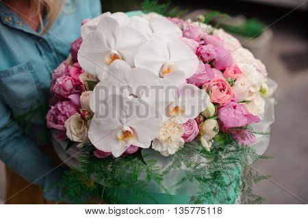 girl holding beautiful mix pink and white flower bouquet in a round box with lid