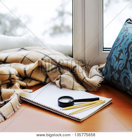 Open Notepad, Magnifier Glass, Pillow, Pencils And Beige Warm Plaid.