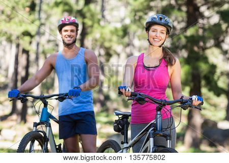 Portrait of cheerful young couple with mountain bikes in forest