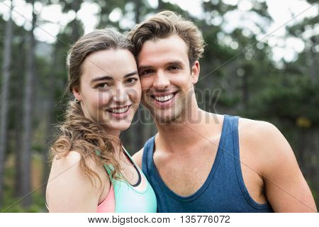 Portrait of smiling young couple standing against trees in forest