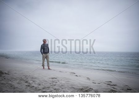 Thoughtful retired man standing on the beach on holidays