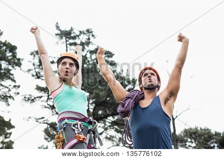 Low angle view of happy couple with arms raised against sky at forest