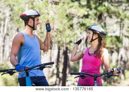Young couple giving high five while riding bicycle at forest