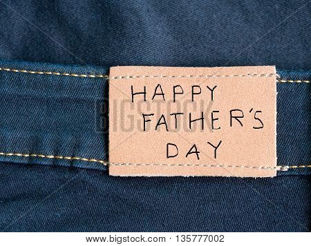 Happy Father's Day celebrations. Love dad. Happy Father's Day written on brown tag of blue jean.
