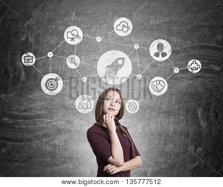 Start up concept with thoughtful young woman standing against chalkboard with rocket ship sketch
