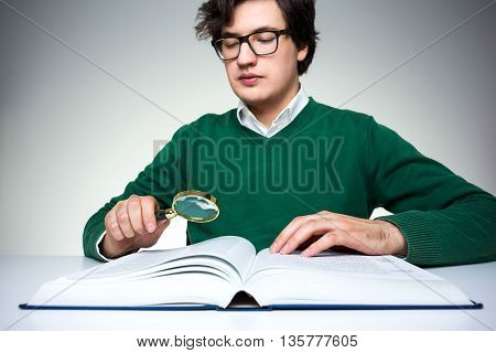 Front view of young man in green pullover sitting at white table and using magnifier to read big book