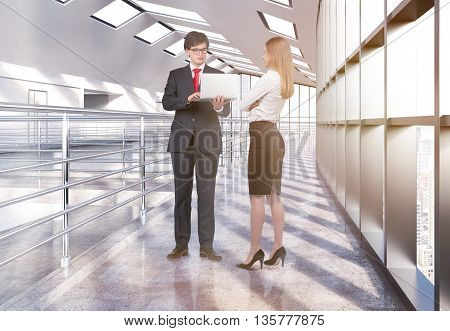 Businesswoman and businessman in laptop standing and discussing project in empty office interior with railings and windows with city view. 3D Rendering