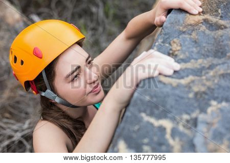High angle view of beautiful woman climbing rock at forest