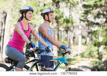 Happy man and woman riding bicycle against trees at forest