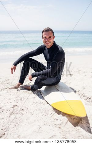Portrait of surfer in wetsuit sitting with surfboard on the beach on a sunny day