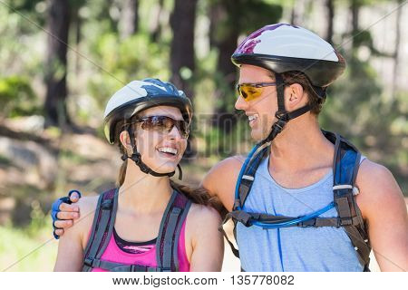 Happy young couple wearing helmets against tree at forest