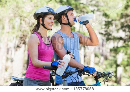 Young couple holding water bottle while riding bicycle at forest