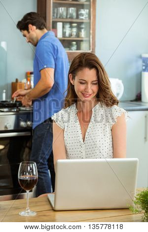 Woman using laptop in kitchen while man cooking food in background