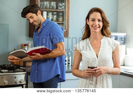 Woman holding wine glass and man cooking with recipe book in kitchen