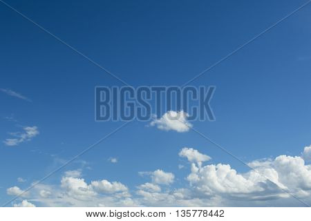 White clouds on the blue sky. Clear sunny weather background.