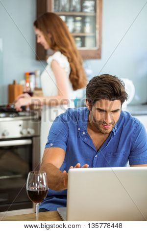 Man using laptop in kitchen while woman cooking food in background