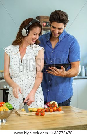 Couple looking at tablet and listening to music on headphones in kitchen at home